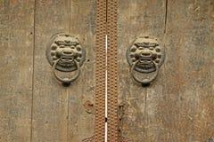 Rusted belägger med metall dörrknackare på en antik anstrykningdörr, i en templ Royaltyfri Bild