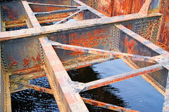 Rusted bridge girders over water Stock Image