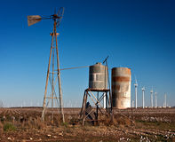 Rusted broken old windmill. Rusted old broken windmill with tanks in a cotton field with wind turbines in the background Stock Images