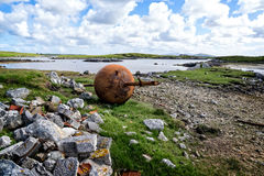 A rusted buoy laying on the shore. A landscape in Scotland on the Island of Uist with a rusted buoy in the grass Royalty Free Stock Images