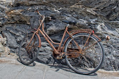 Rusted bycicle on rocks background Royalty Free Stock Photo