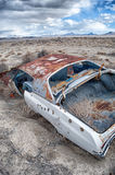 A rusted car in the desert Stock Photo
