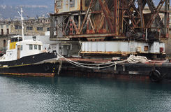 Rusted cargo crane and barge, Trieste old harbour, Italy. Stock Photo
