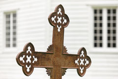 Rusted cemetery cross and white wooden church out of focus. Royalty Free Stock Photos