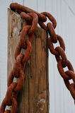 Rusted chain. A rusted chain is bolted on a wooden post Stock Photos