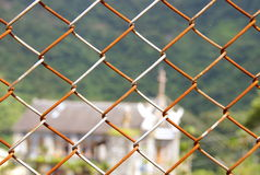 Rusted chain link fence. With church background Royalty Free Stock Image