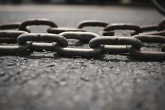 Chain on road. Rusted chain on a road represents something being tied, dragged or bound to something Stock Images