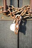 A rusted chainlink and padlock on an old building. This is an image of a length of chain wrapped around the door handles of a building and it is secured with a royalty free stock image