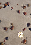 Rusted clock dial on beach sand and stones Stock Photography