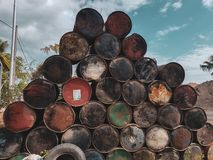 Rusted colorful barrels. Old rusted colorful barrels from fuel or oil products over summer sky background royalty free stock photos