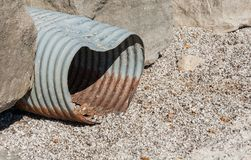 Rusted corrugated metal drain pipe betwen rocks. Royalty Free Stock Photos