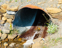 Rusted corrugated metal pipe in rocky ground Stock Photo