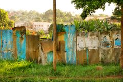 Rusted Corrugated Sheet Metal Wall in Africa. A rusted and breaking corrugated sheet metal wall along the road side in Kampala, Uganda stock images
