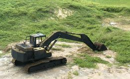 Rusted digger abandoned near to a lush green grassy field Royalty Free Stock Photography