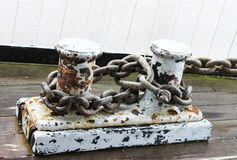 Rusted Dock Cleats with mooring chains attached - grunge -flaking white paint - at marina stock images