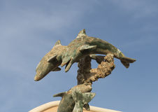 Rusted Dolphin Statue. Pictured is a rusted statue of two dolphins with a blue sky in the background Stock Image