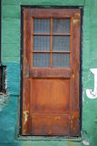 Rusted door. Old rusted door in a green wall Royalty Free Stock Image