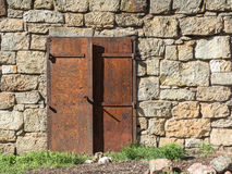 Rusted doors on a stone wall Stock Photos