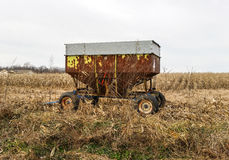 Rusted farm equipment on cloudy winter day Stock Photo