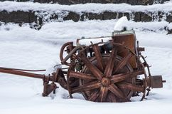 Rusted farm equipment in snow Stock Photo