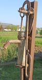Rusted fountain with the lever to pump water Stock Photos