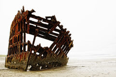 The rusted frame of the wrecked Peter Iredale rests in heavy fog on the northwest Oregon coast. Royalty Free Stock Photography