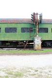 Rusted green railway passenger car with boarded windows and light post track signal. Vertical aspect Royalty Free Stock Photos