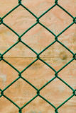 Rusted Green Wire Fence with Grunge Wall  Background. Vertical pattern Stock Photography