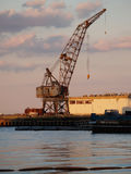 Rusted Grey Crane Harbor Against Cloudy Sky Stock Photo
