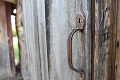 Rusted handle on wooden door. Rusted handle against a wooden door Stock Photo