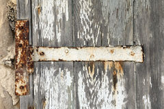 Rusted hinge on old door. With flaking white paint stock image