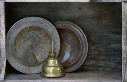 Rusted hubcaps hub caps & oiler on shelf. Rusty hubcaps and brass oil can on old wooden shelf royalty free stock images