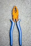 A rusted industrial blue plier tool against concrete background. safety  tetanus