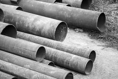 Rusted industrial steel pipes lay on ground, monochrome photo Royalty Free Stock Photography