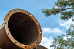 Rusted industrial steel pipes on the tree and blue sky background. Royalty Free Stock Photos