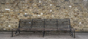 Rusted Iron Bench. A rusted iron bench in front of a brick wall Royalty Free Stock Photos