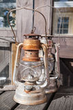 Rusted kerosene lamps stands on wooden table Royalty Free Stock Images