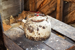 A rusted kettle. An old white rusted kettle on an old desk Royalty Free Stock Photos