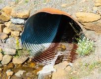 Rusted korrugerade metallröret i stenig jordning Arkivfoto