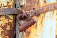 Rusted lock on weathered door. Rusted lock on weathered rusted metal door Royalty Free Stock Photo