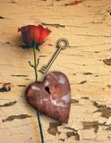 Rusted love. Surrealism. Red rose and rusted heart with keyhole. Golden key Stock Image
