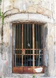 Rusted metal bars on the door of an old abandoned derelict building with cracked walls. Rusted metal bars on the door of an old abandoned derelict building with Royalty Free Stock Photo