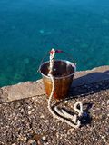 Rusted Metal Bucket and Sea water. A rusted metal bucket and rope used for scooping up sea water to clean freshly caught fish on the pier Stock Images