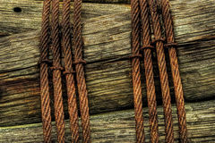 Rusted Metal Cables Wrapped Around Wooden Posts Stock Images