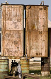 Rusted metal tanks balanced on oil drums Stock Photos