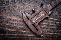 Rusted metal vernier caliper on vintage wooden board constructio Stock Photo