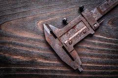 Rusted metal vernier caliper on vintage wooden board constructio Stock Photo