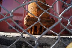 A rusted motor and a fence stock photo