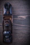 Rusted obsolete planer on wooden board vertical. Image construction concept Stock Photos