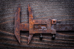 Rusted old-fashioned measuring slide caliper on vintage wooden b Royalty Free Stock Photography